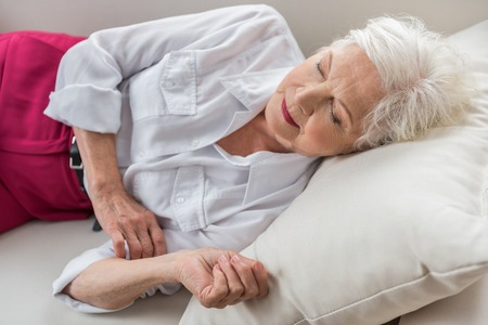 Need to rest. Stylish elegant aged lady is dozing on white couch at her home Standard-Bild