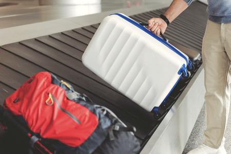 남자가 짐을 가져 가고있다. 그는 공항에서 수하물 테이프 근처에 서있다. 남성 손에 가방 닫습니다. 왼쪽에 공간 복사
