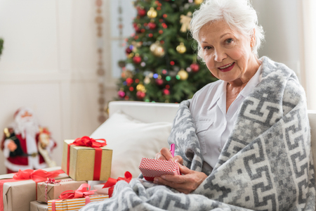 Preparing gifts. Portrait of charming aged woman is sitting on couch among presents and writing wishes. She is looking at camera with joy with Christmas tree on background. Copy space in the left side