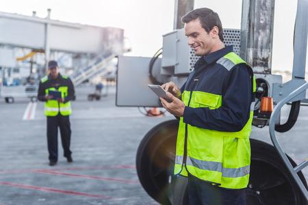 Gelukkige mannelijke arbeider die digitaal apparaat bekijkt