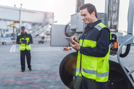 Happy male worker looking at digital device