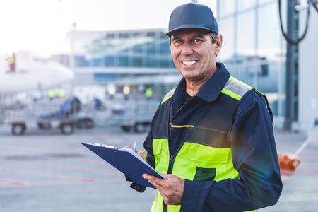 Vrolijke werknemer schrijven document op luchthaven Stockfoto - 86176267