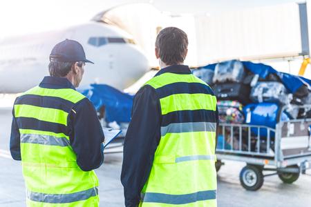 Arbeiders die bagage in vliegveld controleren Stockfoto