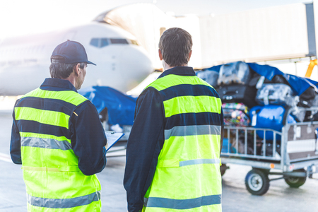 Workers controlling luggage in airdrome Stock Photo