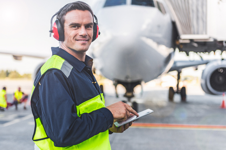 Happy mechanic having job in airdrome Stock Photo