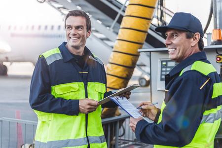 空港での仕事を持っている陽気な技術スタッフ 写真素材
