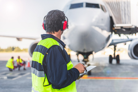 Male worker controlling aircraft and writing information