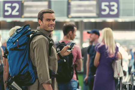 Keeping in touch. Delightful adult man with backpack is holding mobile phone while standing in line for check-in. He is looking at camera with joy. Copy space in the right side