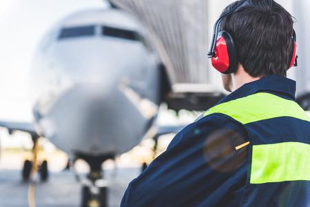 Werktuigkundige die in hoofdtelefoon op luchthaven werken. Hij kijkt naar het vliegtuig terwijl hij terugkeert naar de camera