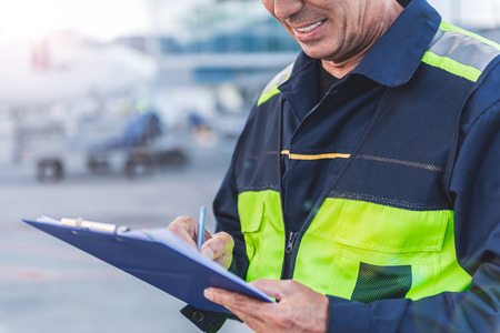 Nadruk op dichte omhoog mannelijke arbeiderswapens die document schrijven terwijl status openlucht bij luchthaven Stockfoto - 86176335