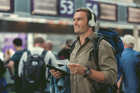 Life is good. Joyful young traveler is holding his tickets and looking aside with smile while listening to music through headphones. Copy space in the left side Banco de Imagens