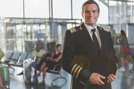 비행장에서 situating 쾌활 한 조종사의 초상화입니다. 그는 카메라를 찾고. 승선 대기자. 공간 복사
