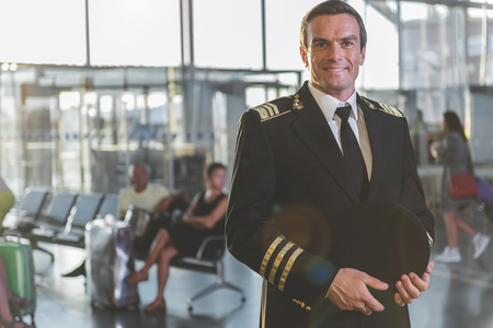 Portrait of cheerful pilot situating at airdrome. He looking at camera. People waiting embarkation. Copy space
