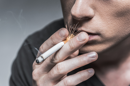 Dangerous smoking. Close up of face of young man smoking cigarette. Focus on needles in filter
