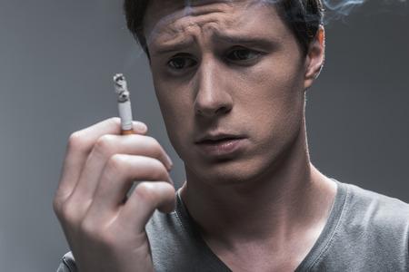 Young man expressing hesitation about smoking 版權商用圖片
