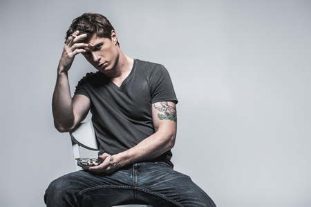 Portrait of stressful guy smoking and looking at camera with disappointment. He is sitting on chair in relaxing pose and holding ashtray. Isolated and copy space