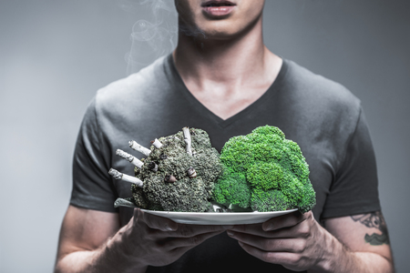 Nicotine is toxic for your health. Close up of arms of young man showing the difference between lungs of smoker and average person. Focus on green fresh broccoli and spoiled one with cigarettes on plate 免版税图像 - 86434595