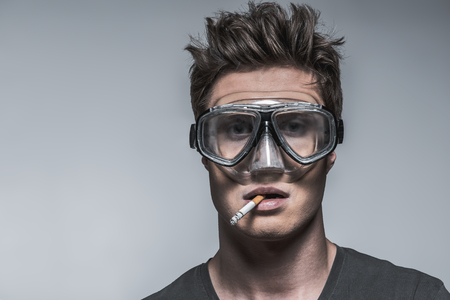 Portrait of thoughtful guy smoking cigarette while keeping item in his mouth. He is wearing diving mask with assurance that it protects him from harm. Isolated and copy space Reklamní fotografie