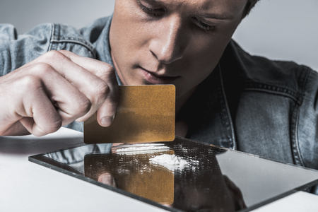 Young man preparing cocaine for sniffing