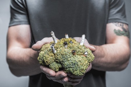 Close up focus on yellowed broccoli with cigarettes inside in male hands. Lungs illness concept