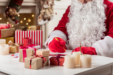 he: Close up of concentrated old man with big white beard writing list of children in notebook. He is sitting in Santa costume. Focus on gift boxes on table Stock Photo