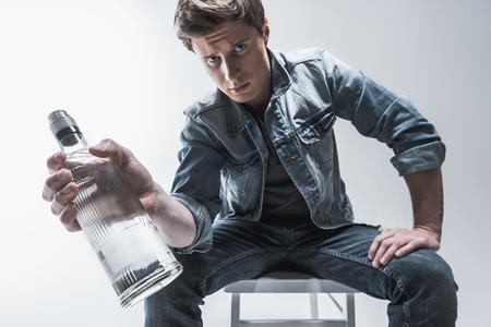 Realmente necesitas esto? Retrato del hombre pensativo que muestra la botella de bebida del alcohol a la cámara. Él está sentado en la silla. Ángulo bajo Foto de archivo - 86434602
