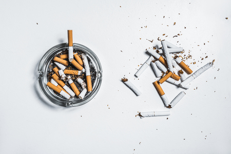 Nicotine is harmful for human health concept. Top view close up of broken cigarettes near ashtray with butts on white table Фото со стока