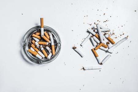 Nikotin ist schädlich für menschliche Gesundheit Konzept . Draufsicht von oben gebrochen Zigaretten in Aschenbecher mit Schraubendreher isoliert auf weißem Tisch