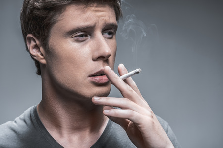 Portrait of young man relieving stress by smoking. He is looking aside pensively. Isolated and copy space
