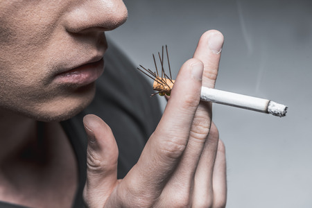 Close up of male hand keeping burning cigarette between fingers. Needles pierce the filter. Isolated and copy space
