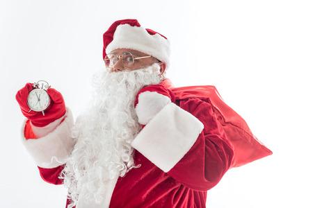 Pronto será el año nuevo. Cintura retrato de alegre padre Frost esperando la medianoche. Él lleva un saco rojo en el hombro y mira a la cámara con seriedad. Aislado Foto de archivo - 86434619