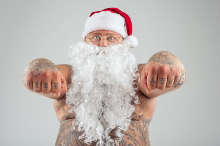 Portrait of brutal fat Santa Claus showing his fists with tattoo on fingers. He is standing with bare abdomen. Focus on male hands. Isolated