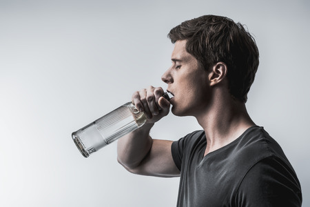 Profile of young man drinking alcohol liquid with pleasure. He is standing with closed eyes while holding big bottle. Isolated and copy space