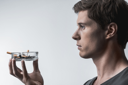 Profile of serious guy holding ashtray with cigarette stubs. He is looking forward with concentration. Isolated and copy space