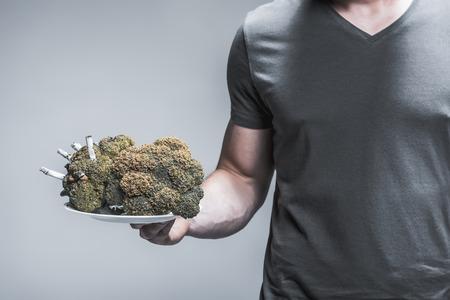 브로콜리에 흡연의 결과를 제시하는 남성 손 닫습니다. 불타는 담배는 야채 안에 해를 끼 웁니다. 스톡 콘텐츠
