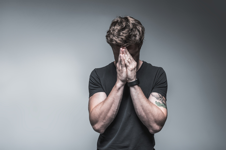 Stressful guy feels pain in his head. He is covering eyes by heads with exhaustion. Isolated on grey background. Copy space