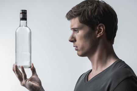 Drowning sorrow in a bottle. Profile of stressful young man looking at alcohol beverage in bottle with sadness. Isolated