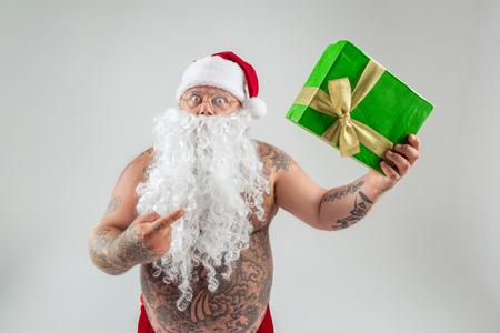 What is this. Portrait of surprised Santa Claus with bare abdomen pointing finger at present box. Isolated on grey background