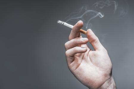 指の間の煙で燃えているタバコを持っている男性の手のクローズ アップ。灰色の背景上に分離。左側のスペースをコピーします。