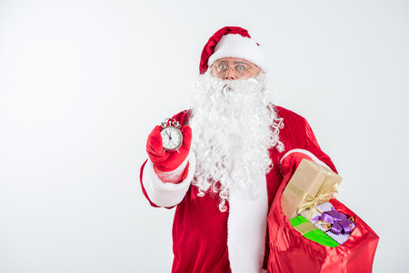 he: Portrait of serious Santa is ready to give presents. He is showing time on clock and holding bag with present boxes. Isolated and copy space