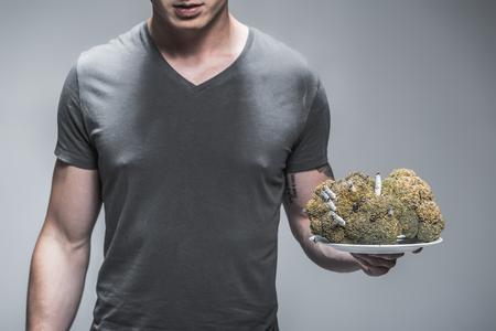 무거운 흡연자는 그런 폐가있다. 젊은 남자의가 까이 서 담배 내부와 큰 버 릇된 브로콜리와 함께 접시를 잡고있다 닫습니다. 회색 배경에 절연