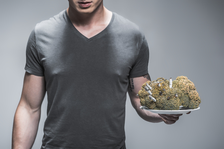 Heavy smoker has such lungs. Close up of young man is holding plate with big spoiled broccoli with burning cigarettes inside. Isolated on grey background