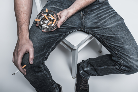 he: Top view close up of young man arm holding ashtray near his legs while sitting on chair. He is keeping burning cigarette in other hand Stock Photo