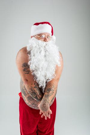 내 옷은 어딨어? 팔에 의해 자신의 뚱뚱한 벌거 벗은 복 부를 닫는 부끄러워 산타 클로스의 초상화. 그의 시신은 모두 문신으로 덮여있다. 외딴 스톡 콘텐츠 - 86434672