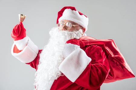 Jingle bell. Waist up portrait of excited Santa Claus ringing the bell while holding red sack. Isolated on grey background