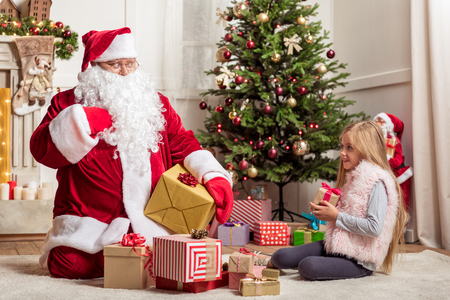 Give me one more present. Cute female child is looking at Santa Claus with hope. Fat man is sitting on floor and gesturing surprisingly Фото со стока