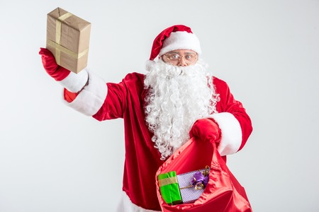 This gift is for you. Portrait of excited grandfather in red and white costume raising wrapped box up. He is standing and showing his full bag. Isolated Banco de Imagens