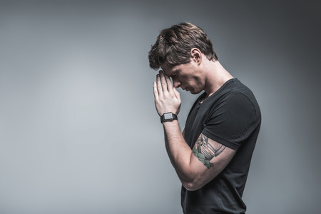 Side view profile of exhausted young man trying to concentrate his mind on serious issue. He is joining palms near face while closing eyes. Isolated and copy space