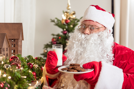 Portrait of joyful Santa Claus eating sweet cookie and drinking glass of milk prepared for him. He is standing near decorative garland at someone home Stock Photo