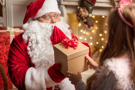 he: You deserve this present. Portrait of excited Santa Claus giving box to female child. He is sitting on comfortable armchair in red costume Stock Photo
